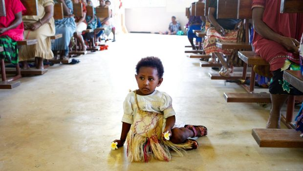 A girl sits it the aisle of the Catholic church during Mass on Manus Island, Papua New Guinea, in 2013. The church is ...