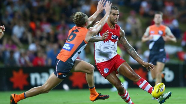 Lachie Whitfield of the Giants tries to charge down a kick from Lance Franklin.