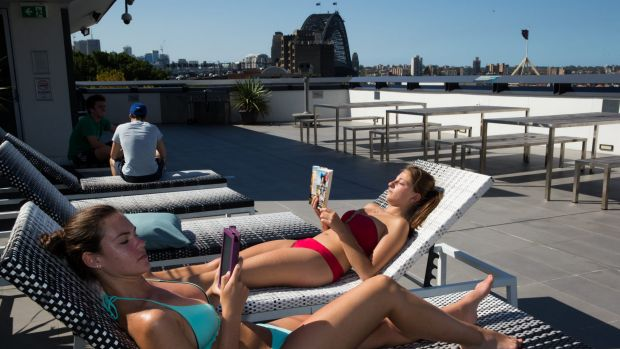 Backpackers Nicole Doyle and Melissa Esposito relax on the roof terrace of the YHA at Sydney's Rocks.
