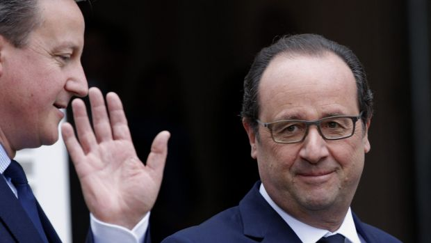 French President Francois Hollande, right, waves as he poses with British Prime Minister David Cameron in Amien, France, ...