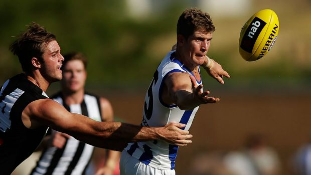 Stretched: Nick Dal Santo of the Kangaroos is challenged by Alan Toovey of the Magpies.