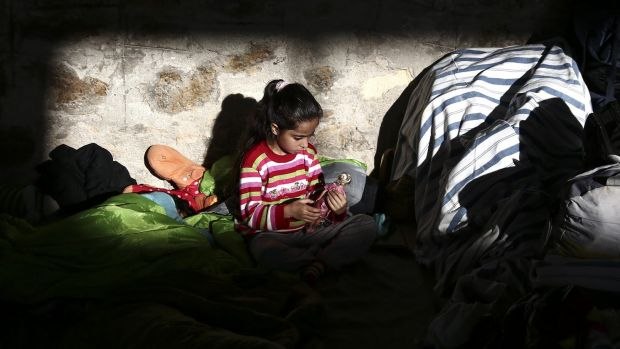 A girl plays inside a temporary shelter for refugees and migrants at the Athens' port of Piraeus.