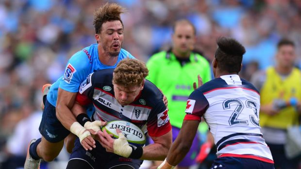 All aboard: Bjorn Basson of the Bulls launches himself at Rebels loose forward Adam Thomson in their Super Rugby match ...