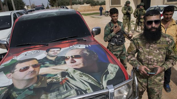 Soldiers in Maarzaf, Syria, stand by a car painted with the faces of Syrian President Bashar al-Assad, left, his ...