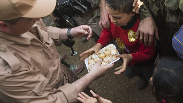 Children reach out for sweets distributed by a Russian soldier in Maarzaf, Syria.