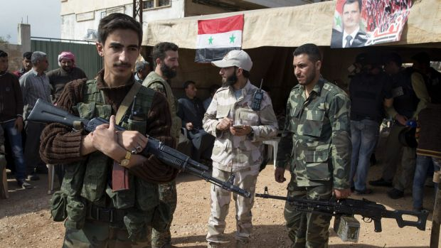 Syrian soldiers guard a tent in Maarzaf, Syria, where local leaders and elders signed a declaration pledging to abide by ...