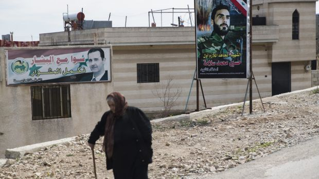 A woman passes banners with a portrait of Syrian President Bashar al-Assad, left, and a killed Syrian officer on a road ...