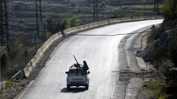 Syrian troops ride on a pick-up truck with a mounted machine gun on a road near Latakia, Syria.