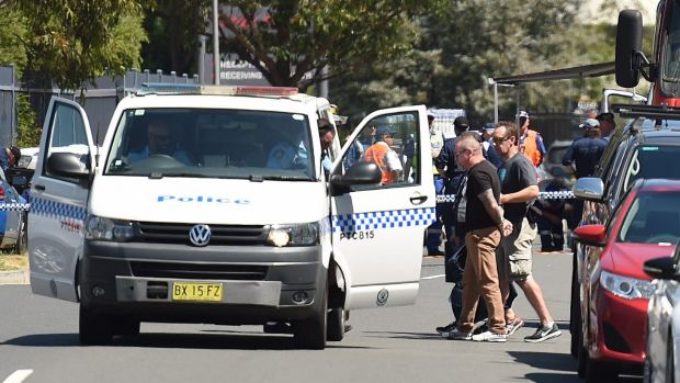 A man is led away in handcuffs near the scene of the stand-off between police and a gunman at a signage business in ...