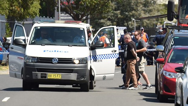 A handcuffed man who has been confirmed by police as being connected to the incident is led into a waiting police van.
