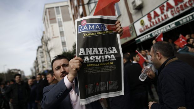 "A man holds Saturday's copy of the newspaper which reads ""the constitution suspended"" as people gathered in support ..."
