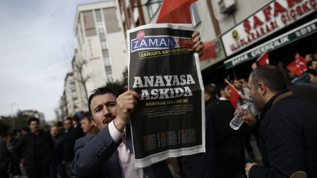 """A man holds Saturday's copy of the newspaper which reads """"the constitution suspended"""" as people gathered in support ..."""