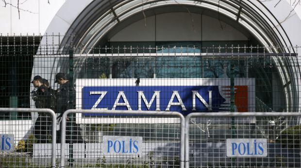Riot police officers walk by the headquarters of Zaman newspaper in Istanbul after it was shut down.