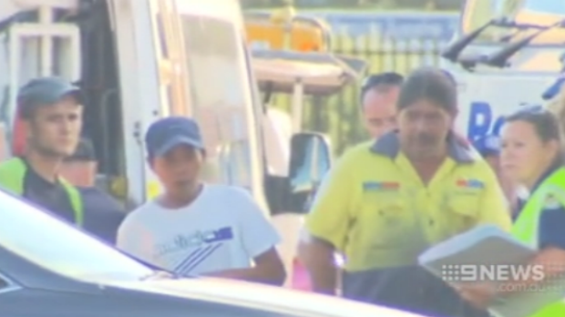 Seksane, left, and another hostage leaves the factory at Ingleburn where they were trapped.