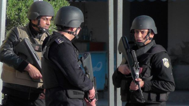 Tunisian police officers take positions during clashes with militants in Ben Guerdane.