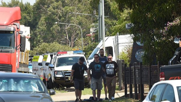 Peter Williams is handcuffed by police and led from the scene during the standoff with police at Ingleburn.