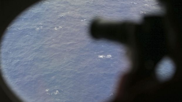 An observer on a Japan Coast Guard Gulfstream aircraft takes photos out of a window while searching for MH370.