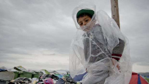 A child wears a plastic cover in the rain in the northern Greek border station of Idomeni on Monday.