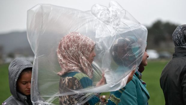A migrant girl shields herself from the rain while waiting in a line for food rations at the northern Greek border ...