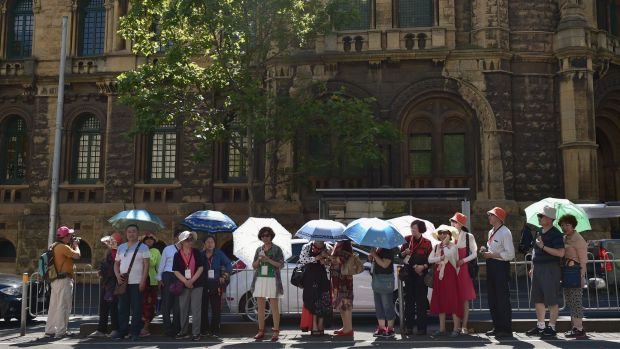 Tourists shield themselves from the hot weather under umbrellas as they wait for a tram on LaTrobe Street in the CBD on ...