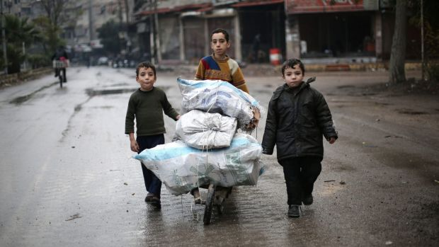 Brothers push a cart of firewood in Eastern Ghouta.
