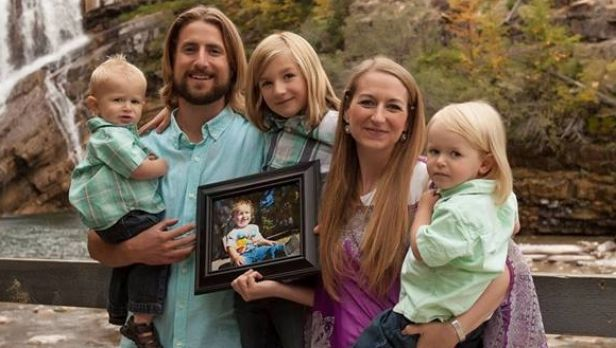 David and Collet Stephan, pictured with their children and a photograph of Ezekiel, who died from meningitis.