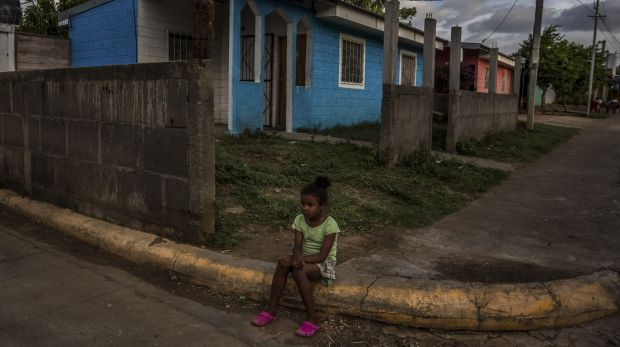 A girl in front of her family's home in a neighbourhood where homes were built by the government as part of the Houses ...