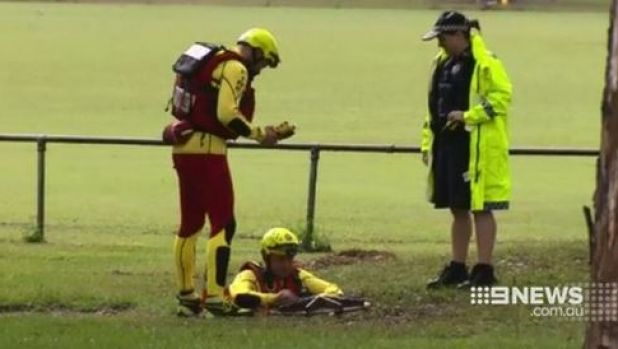 Emergency crews search an Indooroopilly drain for students feared missing.