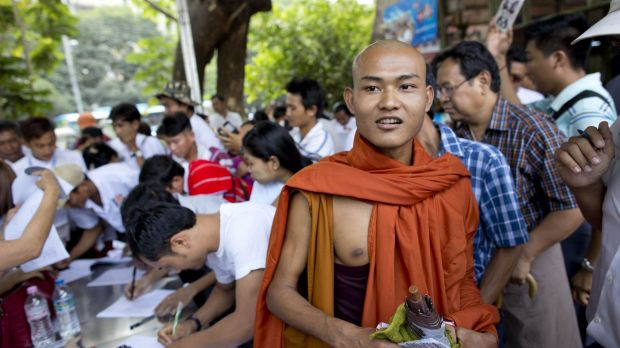 A Buddhist monk walks as others sign an attendance register during a rally by Myanmar nationalist groups on Sunday in ...