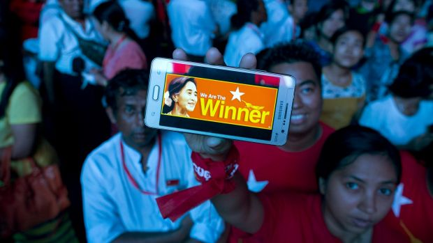 A supporter of Myanmar's National League for Democracy party displays her mobile phone with a picture of Aung San  Suu ...