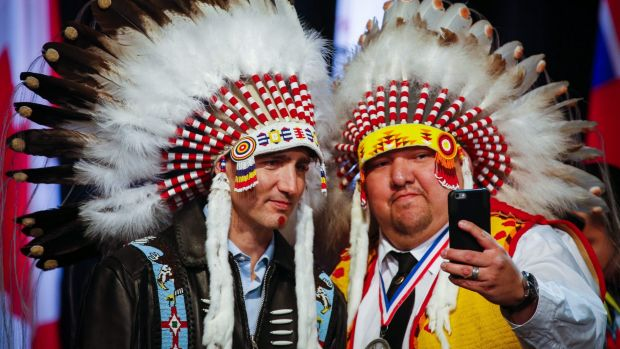 Canadian Prime Minister Justin Trudeau, left, poses for a selfie with an elder after receiving a ceremonial headdress ...