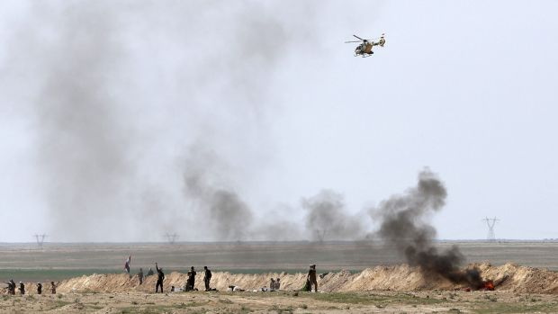 An Iraqi Army helicopter flies over security forces and Popular Mobilisation forces at the front line with Islamic State ...