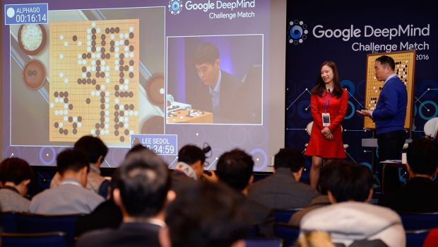 An audience watches a screen showing the live broadcast of the Google DeepMind challenge match in Seoul.