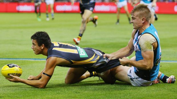 Getting shirty: Tiger Daniel Rioli is tackled by Port Power's Ollie Wines.