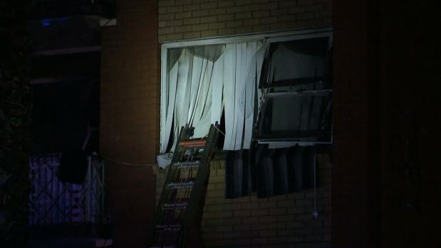 A woman, 27, was rescued from the windowsill of her burning apartment after dropping her two children to safety.