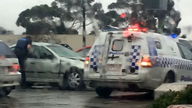 Police speak to a witness of the Geelong shoot-out in a KFC car park on Thursday.