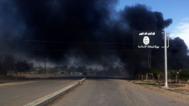 Smoke billows behind an Islamic State street sign during clashes between the terrorist group and Iraqi security forces ...
