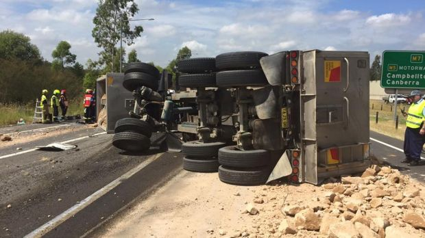 The truck was carrying a load of sand and rocks, which spilled onto the M7.