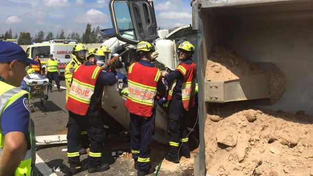 Firefighters work to free a trapped truck driver on the M7.
