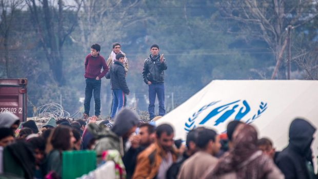 Migrants wait to receive aid in the Greek village of Idomeni  on Thursday.