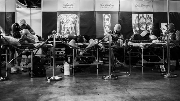 Tattoo artists working on clients at the event.