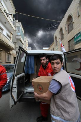 Homs, Syria, 15 February 2012: Local volunteers deliver aid in Homs area of Baba Amr (Central Syria). In the background ...