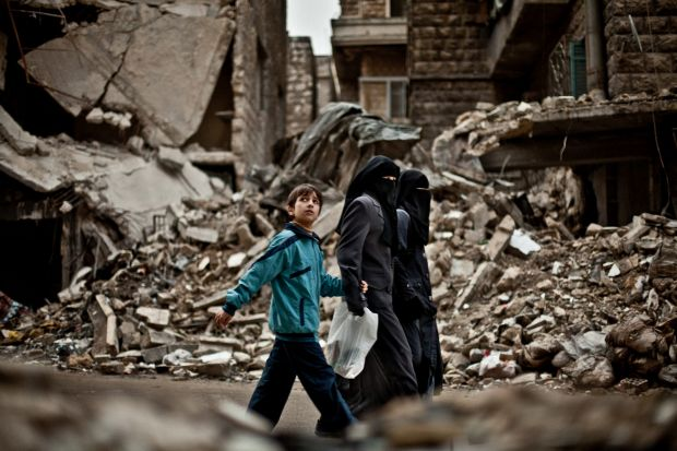 Aleppo, Syria, February 2013: A child observes as a military jet flies over the ruins of the Al Mashad neighborhood.
