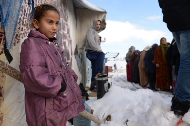 Bitterly cold, living in tents Bekaa valley, Lebanon, January 2015: A child waits for her parents to receive emergency ...