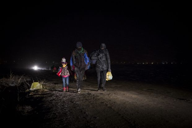 Macedonia-Serbia border, January 2016. Refugees walk through the night across the border in the snow and freezing ...