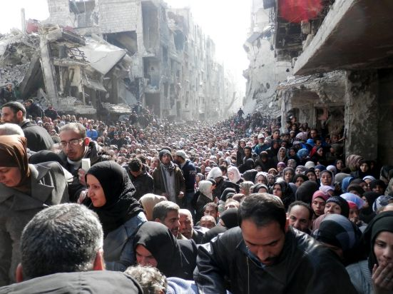 Yarmouk refugee camp, Syria, January 2014: Residents wait to receive food aid distributed by the UN Relief and Works ...