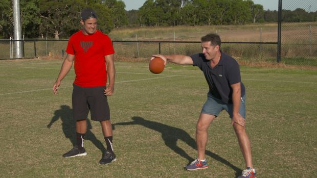 Game time: Stefanovic puts Hayne through his paces at American football.