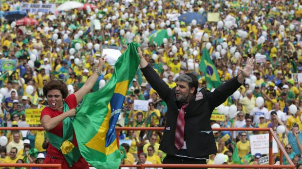 Demonstrators dressed as Brazilian President Dilma Rousseff, left, and former president Lula, gesture to the crowd ...