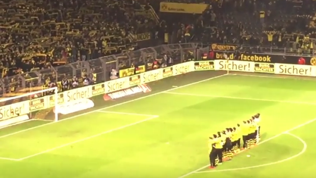 Tribute: Borussia Dortmund players sing with their fans in honour of a fan who died during their game against Mainz 05.