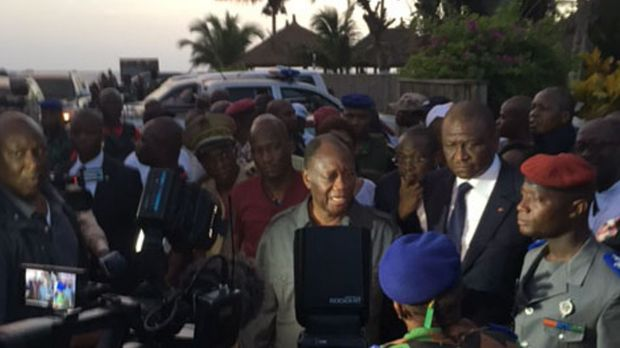 Ivory Coast's President Alassane Ouattara, centre, visits the area were gunmen attacked people in Grand Bassam, on Sunday.